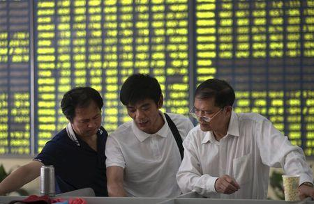 Investors talk in front of an electronic board showing stock information, filled with green figures indicating falling prices, at a brokerage house in Nantong