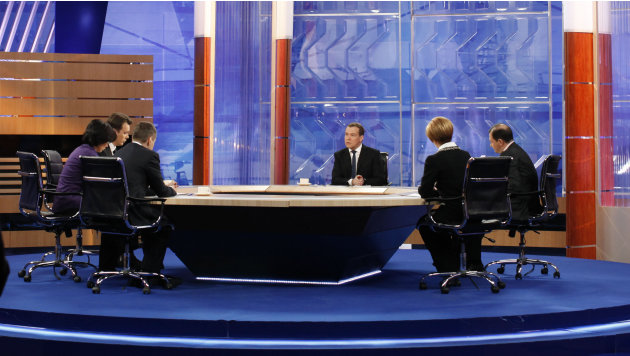 Russian Prime Minister Dmitry Medvedev, center, speaks during live televised interview from Moscow's Ostankino TV Center on Friday, Dec. 7, 2012.  Medvedev answers questions from TV hosts of Russia Fe