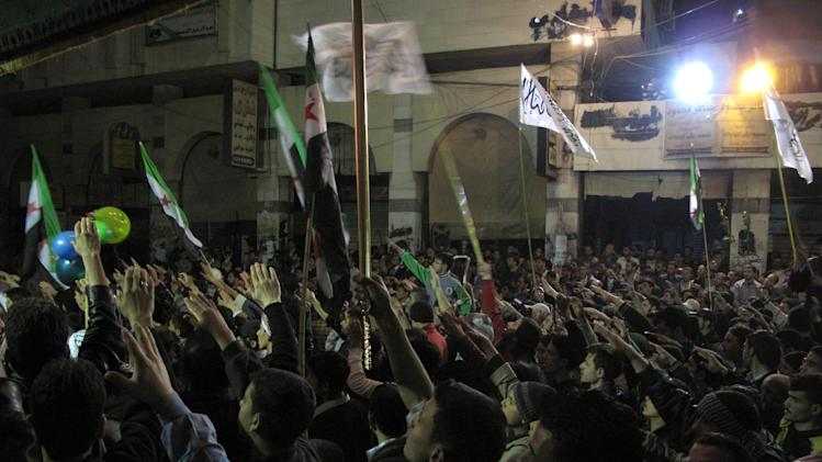 In this Wednesday, April 4, 2012 photo, Syrians raise their hands vowing to continue fighting until President Bashar Assad's regime falls during a protest in a neighborhood in Damascus, Syria. Syrian troops launched a fierce assault on a Damascus suburb Thursday with activists describing it as one of the most violent attacks since the year-old uprising began. (AP Photo)