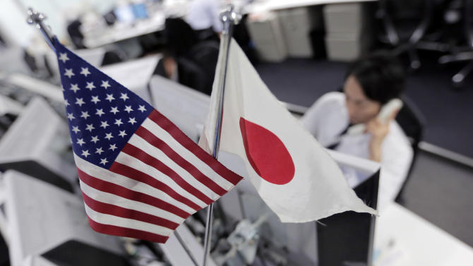 Money traders work under flags of the United States and Japan at a foreign exchange firm in Tokyo Friday,  Dec. 21, 2012. The dollar was little changed against other major currencies as traders await developments from budget talks in Washington. (AP Photo/Itsuo Inouye)