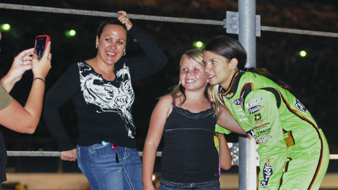 Danica Patrick, right, poses for a photo with fans during a red-flag delay in the NASCAR Daytona 500 auto race at Daytona International Speedway in Daytona Beach, Fla., Monday, Feb. 27, 2012. (AP Photo/Barkley Wyckoff)