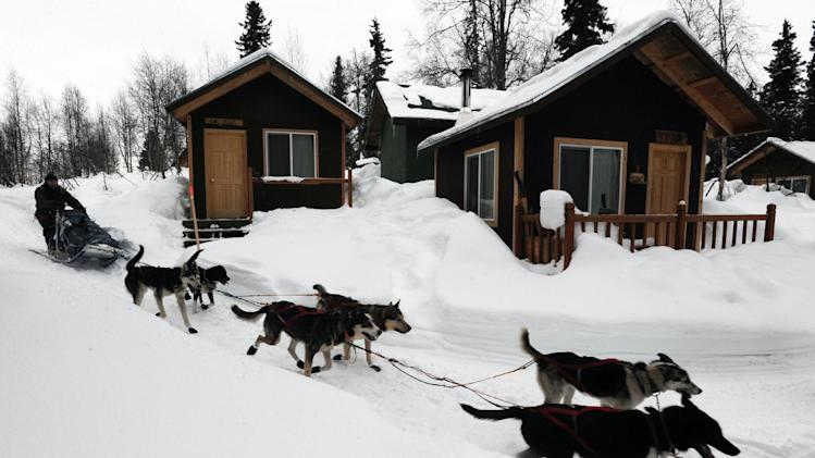 Robert Bundtzen drives his team past cabins at Winterlake Lodge at the Finger Lake checkpoint in Alaska during the Iditarod Trail Sled Dog Race on Monday, Mar. 4, 2013. (AP Photo/The Anchorage Daily News, Bill Roth)