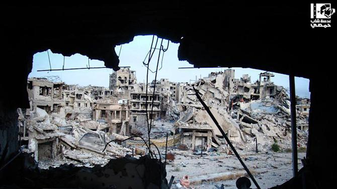 In this picture taken on Wednesday, June 5, 2013, citizen journalism image provided by Lens Young Homsi, which has been authenticated based on its contents and other AP reporting, shows damaged buildings are seen in the Jouret al-Chiyah neighborhood, Homs province, central Syria. Syrian troops and their Lebanese Hezbollah allies captured a strategic border town Wednesday after a grueling three-week battle, dealing a severe blow to rebels and opening the door for President Bashar Assad's regime to seize back the country's central heartland. The regime triumph in Qusair, which Assad's forces had bombarded for months without success, demonstrates the potentially game-changing role of Hezbollah in Syria's civil war. (AP Photo/Yong Homsi Lens)