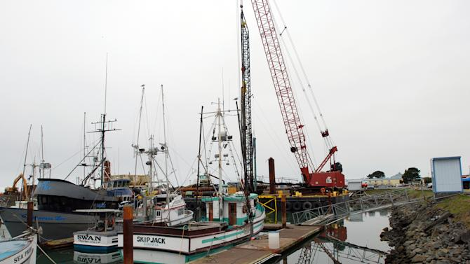 An Oct. 26, 2012 photo shows a large driling rig, at right, waiting for a custom drill bit to install bigger and stronger dock pilings to take the place of docks destroyed by the 2011 tsunami from Japan. Once it overcomes some construction delays, the port hopes to have the West Coast's first harbor designed to withstand the kind of tsunami expected to hit every 50 years. Due to the formation of the sea floor and the configuration of the harbor, Crescent City regularly takes the biggest hit of any port on the West Coast from tsunamis, whether they come from Chile, Alaska or Japan. (AP Photo/Jeff Barnard)