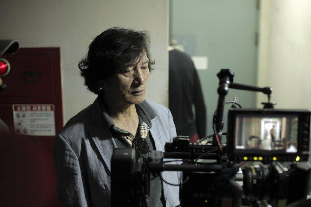 "In this undated photo released on Friday, Oct. 5, 2012 by Busan International Film Festival, South Korean director Chung Ji-young looks at a monitor for his movie ""National Security"" in South Korea. The film based on the memoir of a democracy activist who was tortured in the 1980s by South Korea's military rulers is provoking discussion about the country's not-so-distant authoritative past and the influence it will have on this year's presidential election. (AP Photo/Busan International Film Festival) EDITORIAL USE ONLY"