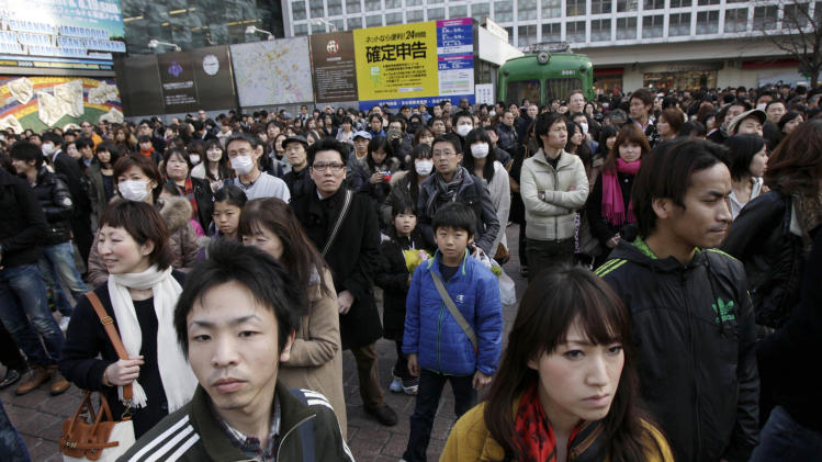 People stop for a moment of silence to mark the anniversary of the earthquake and tsunami which devastated northeastern Japan, at the Shibuya crossing in Tokyo, Sunday, March 11, 2012. (AP Photo/Greg Baker)