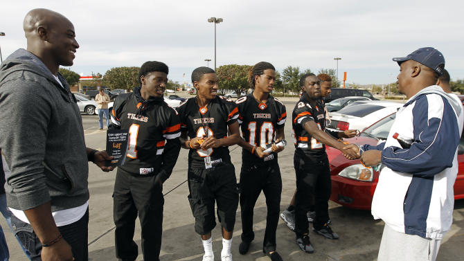Dallas defensive lineman DeMarcus Ware, left, leads the captains of the Lancaster Tigers high school football team around town to drum up support among the residents for their upcoming playoff game during the Duracell Trust Your Power NFL Campaign event on Tuesday, Nov. 13, 2012inLancaster, Texas. (Photo by Brandon Wade/Invision for Duracell/AP Images)