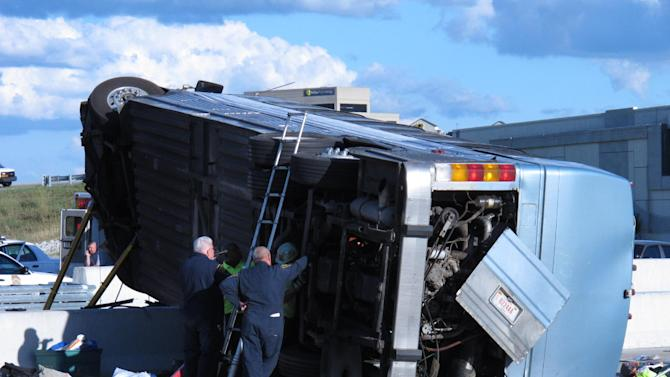 Indiana State Police investigators inspect the underside of a bus that crashed Saturday, July 27, 2013, on Indianapolis' far north side while carrying teenagers returning from a summer camp in Michigan. Three people were killed and 26 others were taken to local hospitals following the crash, which occurred when the bus exited an interstate ramp and crashed into a concrete retaining wall. Investigators don't yet know what caused the crash about a mile from its destination, Colonial Hills Baptist Church. (AP Photo/Rick Callahan).