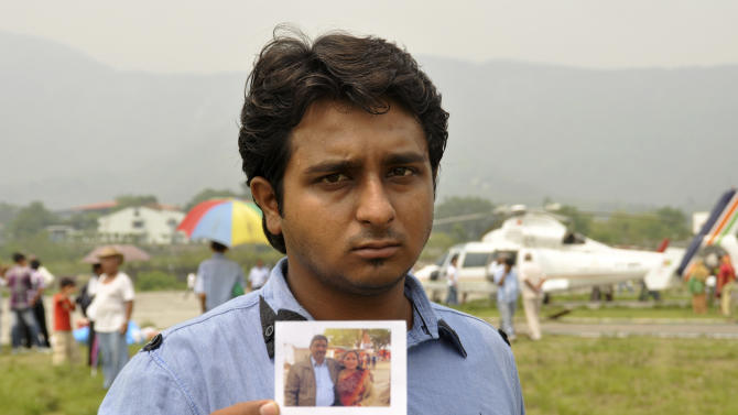 Neelesh, only one name available, shows a photograph of his parents, who went missing during their pilgrimage in Kedarnath in the northern Indian state of Uttrakhand after flash floods and landslides, waits at the airport in Dehradun, India, Saturday, June 22, 2013. Soldiers were working to evacuate tens of thousands of people still stranded Saturday in northern India where nearly 600 people have been killed in monsoon flooding and landslides. (AP Photo)