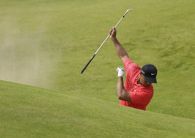 Tiger Woods of the United States reacts after failing to hit the ball out of the bunker on the sixth hole at Royal Lytham &amp; St Annes golf club during the final round of the British Open Golf Champions