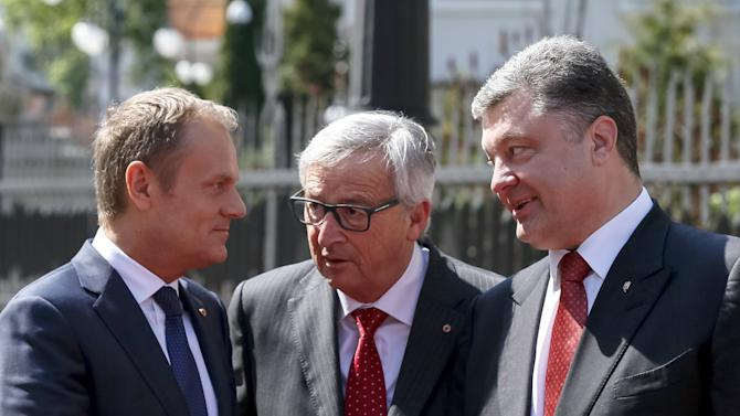 European Council President Donald Tusk gestures as he talks to European Commission President Jean Claude Juncker and Ukrainian President Petro Poroshenko before their meeting in Kiev