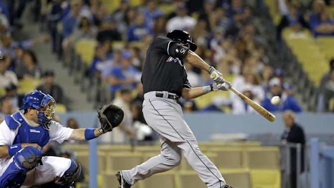 Miami Marlins' Derek Dietrich connects on a three-run homer against Los Angeles Dodgers catcher A.J. Ellis, left, watches in the fourth inning of a baseball game in Los Angeles, Friday, May 10, 2013. (AP Photo/Reed Saxon)