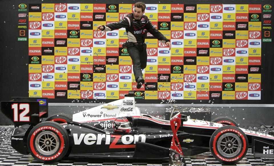 IndyCar driver Will Power, of Australia, jumps off his car at the winner's podium as he celebrates winning the the IndyCar Sao Paulo 300 in Sao Paulo, Brazil, Sunday, April 29, 2012. (AP Photo/Andre Penner)
