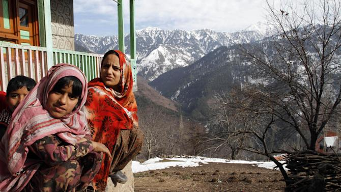 """Kashmiri villagers rest outside their home  near the Line of Control (LOC), the line that divides Kashmir between India and Pakistan, in Churunda village, about 150 Kilometers (94 miles) northwest of Srinagar, India, Tuesday, Jan. 15, 2013. India's relations with archrival Pakistan """"cannot be business as usual"""" in the wake of a spate of attacks in Kashmir, Prime Minister Manmohan Singh said Tuesday in a statement that threatens to ratchet up tensions in the wake of the Himalayan violence. A series of tit-for-tat attacks, including the beheading of an Indian soldier, across the LOC that divides the Himalayan region has killed two Pakistani and two Indian soldiers over the past 10 days. (AP Photo/Mukhtar Khan)"""