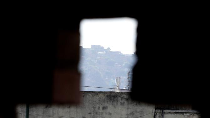 """A poster of Venezuela's President Hugo Chavez is seen through a cross-shaped window, from inside the military hospital's chapel, in Caracas, Venezuela, Tuesday, March 5, 2013. A brief statement read on national television by Communications Minister Ernesto Villegas late Monday carried the sobering news about the charismatic 58-year-old leader's deteriorating health. Villegas said Chavez is suffering from """"a new, severe infection."""" The state news agency identified it as respiratory. (AP Photo/Ariana Cubillos)"""