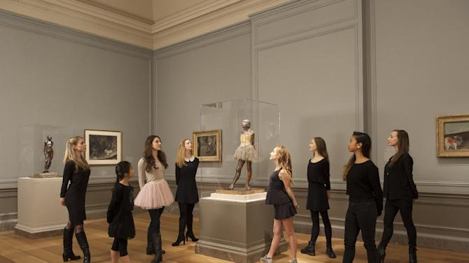 """This undated handout photo provided by The Kennedy Center shows the Little Dancer Company visit to the """"Little Dancer Aged Fourteen"""" sculpture by Edgar Degas, at the National Gallery of in Art in Washington. """"Little Dancer Aged Fourteen,"""" a famous sculpture by Edgar Degas that can be seen in museums around the world, is coming to life in a new musical debuting on the Kennedy Center stage in Washington. The new $7 million production opening for previews Saturday is the brainchild of playwright and lyricist Lynn Ahrens, composer Stephen Flaherty and director and choreographer Susan Stroman. The show was born out of a love of dance and their shared interest in one of the most important sculptures at the National Gallery of Art that depicts a defiant 14-year-old dancer who posed for Degas. (AP Photo/The Kennedy Center)"""