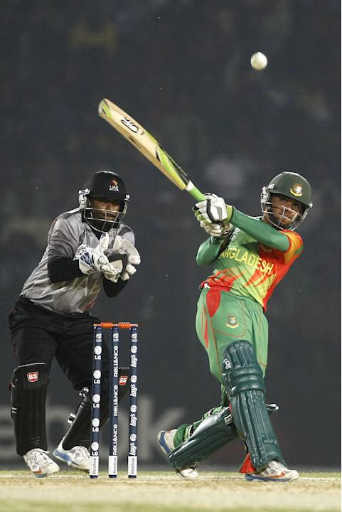 Bangladeshi cricketer Mominul Haque plays a shot in front of United Arab Emirates' wicketkeeper Swapnil Patil during a warm-up cricket match ahead of the Twenty20 World Cup Cricket in Fatullah, ne