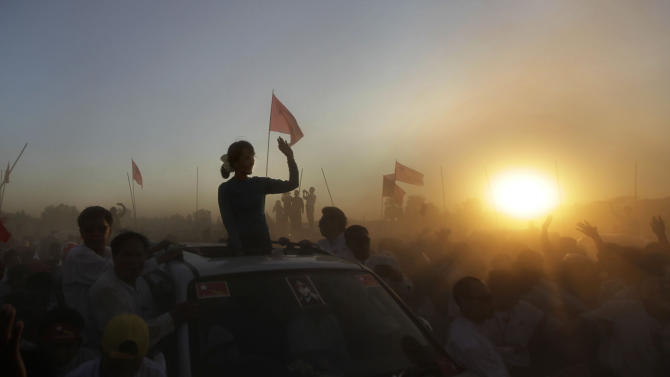 FILE - In this Feb. 26, 2012 file photo, Myanmar's pro-democracy icon Aung San Suu Kyi is silhouetted by the setting sun as she arrives to deliver her speech during an election campaign rally in Thongwa village, some 50 kilometers (31 miles) from Yangon, Myanmar. Twenty-four years ago Aung San Suu Kyi left Europe for what was then a military-controlled nation called Burma. She returns Wednesday, June 13, 2012 the icon of Myanmar's democracy movement to a continent eager to hear from her whether the country's recent reforms truly spell the end of its cruel dictatorship. (AP Photo/Altaf Qadri, File)