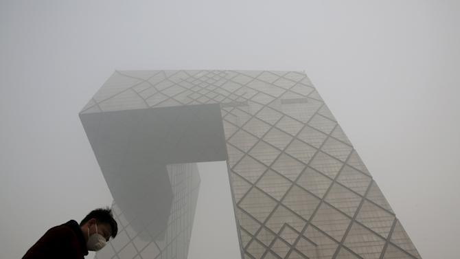 A man wearing a mask walks past the China Central Television (CCTV) building during a heavily polluted day in Beijing