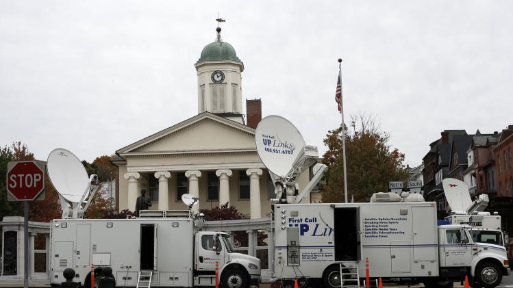News trucks line the street in front of the Centre County Courthouse Monday, Oct. 8, 2012, in Bellefonte, Pa. Former Penn State University assistant football coach Jerry Sandusky is scheduled to be sentenced Tuesday for sexually abusing 10 boys in a scandal that rocked the university and brought down coach Joe Paterno. (AP Photo/Matt Rourke)
