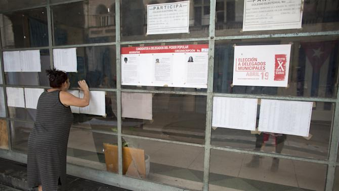 A woman looks through the window of a polling station to be used for the municipal elections in Havana
