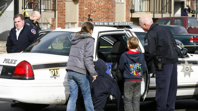 Two children are led to a police car after a quadruple homicide at Tulsa's Fairmont Terrace apartment complex on Monday, January 7, 2013. Police said a 4-year-old was taken into productive custody after being found inside an apartment where four women were shot to death.    (AP Photo/Tulsa World, Matt Barnard )   TV OUT; TULSA OUT