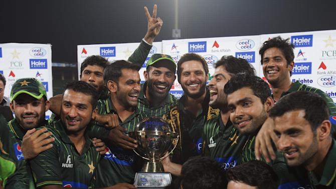 Pakistani cricket players celebrate their victory over Zimbabwe at the Gaddafi Stadium in Lahore, Pakistan, Sunday, May 24, 2015. The Twenty20 matches Friday and Sunday mark a return of international cricket to Pakistan for the first time since gunmen attacked buses carrying the Sri Lankan cricket team and match officials in this eastern city six years ago. Security has been beefed up for the matches. (AP Photo/B.K. Bangash)