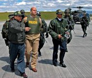 This file photo shows National Police officers escorting the leader of the rebel group FARC, known as Simon Trinidad (2-L), to a Colombian military airport in Bogota, in 2004. Colombia's leftist rebels said on Friday they are hoping the United States will allow Trinidad, held there, to participate in peace negotiations starting next month