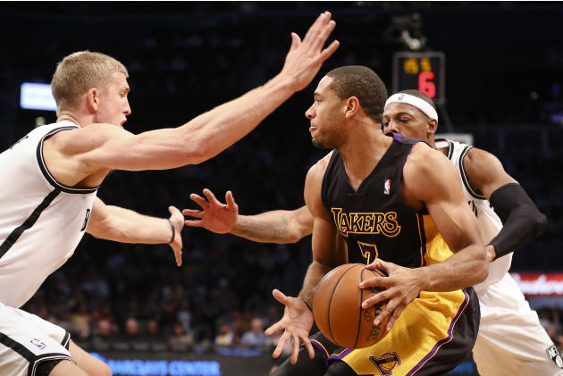 Los Angeles Lakers small forward Xavier Henry (7) looks to pass through Brooklyn Nets power forward Mason Plumlee, left, and small forward Paul Pierce, right, in the second half of an NBA basketball g