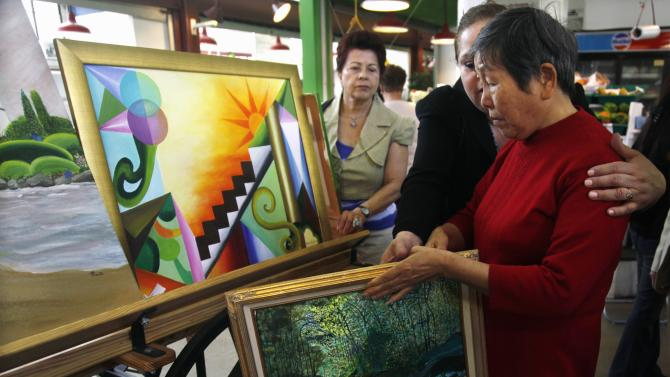 """In this Tuesday, May 10, 2011 picture, Piedad Gerena, center, helps Wang Huaxian, 73, collect paintings as they prepare to leave La Marqueta, an East Harlem marketplace in New York.  Gerena, who give art lessons to seniors, travels with her students by a school bus provided through the city's """"Age-Friendly NYC"""" program. (AP Photo/Bebeto Matthews)"""