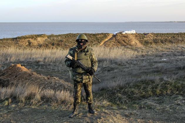 A Ukrainian soldier stands at a checkpoint near the village of Salkovo