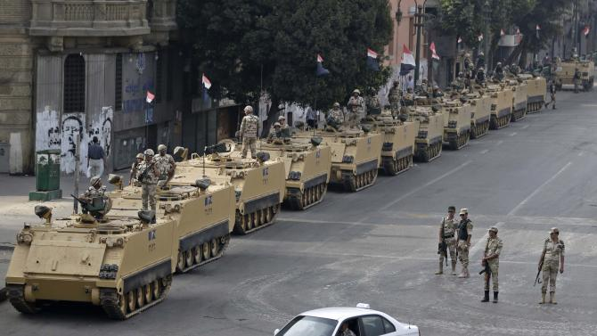 "In this Friday, Aug. 16, 2013 photo, Egyptian army soldiers take their positions on top and next to their armored vehicles to guard an entrance of Tahrir square, in Cairo, Egypt. Egypt's capital has long been proud of its nickname, ""Mother of the World"" _ a city of 18 million, buzzing and lively, fun-loving and never sleeping. But Cairo's spirit has been deeply wounded 32 months of turmoil, bloodshed, two ""revolutions,"" and a military coup. Cairenes now talk of a new callousness and edginess, suspicion of outsiders, bitter divisions between Islamists _ all fueling a longing for normalcy. (AP Photo/Hassan Ammar)"