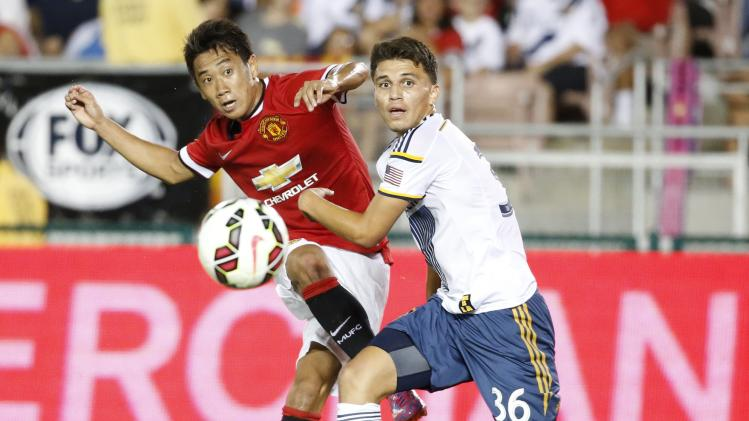 Manchester United's Kagawa of Japan attempts to score past Los Angeles Galaxy's Sorto during the second half of their international soccer friendly match in Pasadena