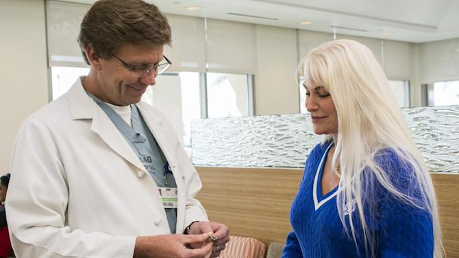 Surgeon Dr. John Lipham, left, talks to his patient, Tricia Carr, at the Hoag Memorial Hospital Presbyterian in Newport Beach, Calif. on Thursday, April 4, 2013, about the Linx device she had implanted. The small band of magnetic beads is used to treat chronic heartburn. The bracelet-like device is implanted around a weak muscle at the base of the throat that doesn't close as it should and helps prevent stomach acid from splashing back into the throat. Swallowing food will overcome the magnetic attraction and allow the beads to separate, allowing food and liquid to pass normally into the stomach. (AP Photo/Damian Dovarganes)