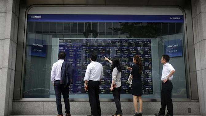 Pedestrians stand in front of a stock quotation board displaying various stock prices outside a brokerage in Tokyo July 29, 2013. REUTERS/Yuya Shino/Files