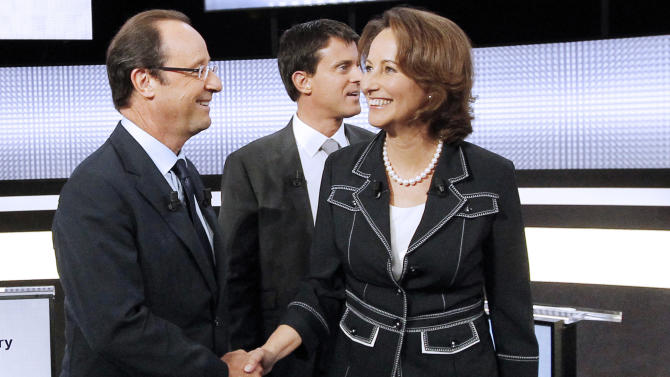 FILE - In this Sept. 15, 2011 file photo, candidates for the 2011 French Socialist party primary elections Francois Hollande, left, shakes hands with Segolene Royal, right, while Manuel Valls, center back, looks on before a televised debate in Paris. Royal, French President Francois Hollande's former partner, has been named Wednesday April, 2, 2014 as Minister of Environment and Energy. Valls is now Prime Minister. (AP Photo/Patrick Kovarik, Pool-File)