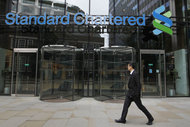 A man walks by the headquarter of Standard Chartered bank in the City of London, Tuesday, Aug. 7, 2012. Shares in Standard Chartered PLC dropped sharply on Tuesday as investors reacted to U.S. charges that the bank was involved in laundering money for Iran. The charges against Standard Chartered were a shock for a bank which proudly described itself recently as &quot;boring.&quot; (AP Photo/Sang Tan)
