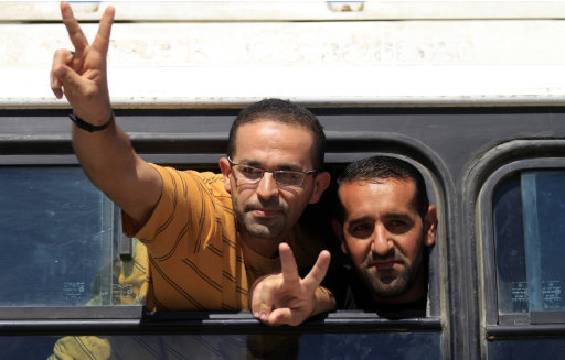 Freed Palestinian prisoners from Israeli jails flash the victory sign from a bus leaves the Egyptian side of Rafah crossing terminal to Gaza Strip, Rafah, Egypt Tuesday, Oct. 18, 2011. Looking dazed, a thin and pale Gilad Schalit emerged from a pickup truck Tuesday under the escort of his Hamas captors and the Egyptian mediators who helped arrange the Israeli tank crewman's release after more than five years in captivity. (AP Photo/Khalil Hamra)