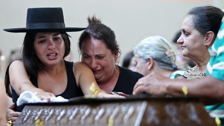 Relatives cry next to a coffin at a gymnasium where bodies were brought for identification in Santa Maria city, Rio Grande do Sul state, Brazil, Sunday, Jan. 27, 2013. Flames raced through a crowded nightclub in Santa Maria early Sunday, killing more than 230 people as panicked partygoers gasped for breath in the smoke-filled air, stampeding toward a single exit partially blocked by those already dead. (AP Photo/Nabor Goulart)