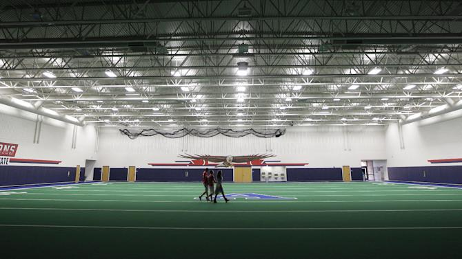 Students walk across the indoor practice field that is part of the new  $60 million football stadium at Allen High School Tuesday, Aug. 28, 2012 in Allen, Texas. Allen High School northeast of Dallas christens the stadium Friday night with a matchup against defending state champion Southlake Carroll. While other school districts are struggling to retain teachers and keep classroom sizes down, Allen voters approved a $119 million bond issue that pays for the stadium and other district facilities. (AP Photo/LM Otero)
