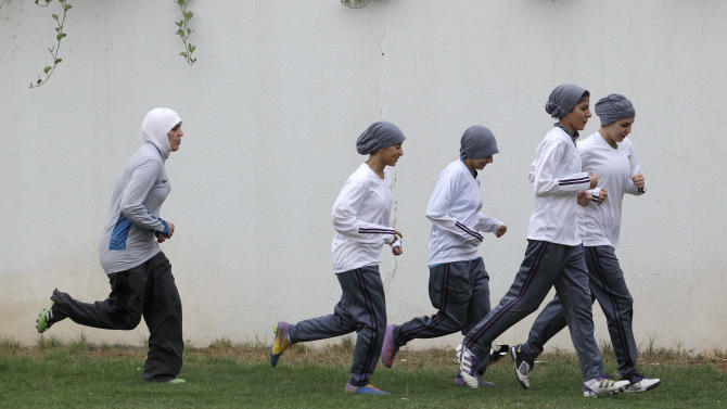FILE - In this May 21, 2012 file photo, members of a Saudi female soccer team practice at a secret location in Riyadh, Saudi Arabia. Saudi Arabia's official press agency says the Education Ministry has allowed private female schools to hold sports activities within the Islamic Sharia laws. SPA said Saturday, May 4, 2013 that the ministry issued directives ordering private female schools to provide appropriate places and equipment for such activities, adhere to wearing decent dress and that Saudi women teachers should be given priority in supervising these activities.(AP Photo/Hassan Ammar, File)