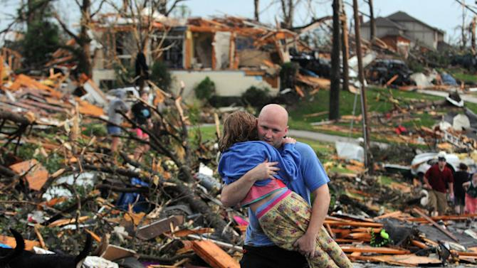 FILE - In this May 22, 2011 file photo, a man carries a young girl who was rescued after a tornado hit Joplin, Mo. In 2011 the United States saw one of the busiest tornado seasons in generations: Nearly 1,700 tornadoes that killed 553 people. With the planet heating up, many scientists seem fairly certain some weather elements like hurricanes and droughts will worsen. But as the traditional season nears, scientists are still trying to figure out if there be more or fewer tornadoes as global warming increases. (AP Photo/Mike Gullett, File)