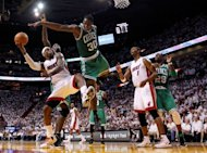 Miami Heat's LeBron James (L) goes for a shot as Boston Celtics' Brandon Bass (2nd R) defends during the second half in game seven of their NBA Eastern Conference Finals on June 9. Miami took the best-of-seven Eastern Conference championship series four games to three to reach the NBA Finals