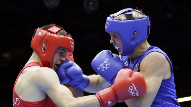 In this Aug. 2, 2012, photo, Ireland's Darren O'Neill, left, fights Germany's Stefan Hartel during their men's middle weight 75-kg boxing match at the 2012 Summer Olympics in London. O'Neill quit his job as an elementary school teacher in Dublin seven months ago to train full-time for the Olympics _ and isn't sure he'll get the job back when he goes home.  The majority of Olympians have little or no corporate backing and work one, two, even seven jobs while finding time to train to face fully-funded pros. (AP Photo/Andrew Medichini)