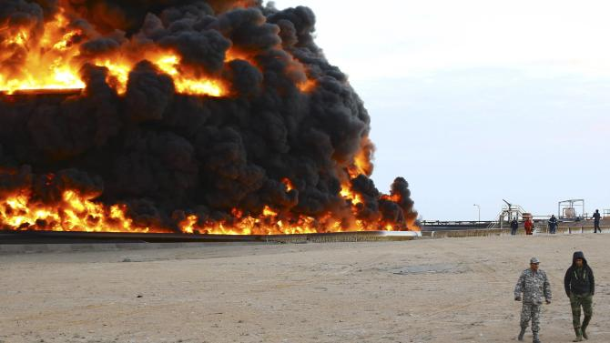 Firefighters try to put out the fire in an oil tank in Es Sider port
