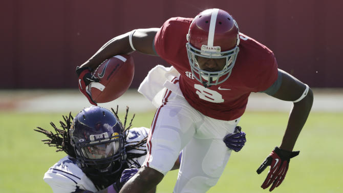 Western Carolina defensive back Jaleel Lorquet (2) stops Alabama wide receiver Amari Cooper (9) after a reception during the first half of an NCAA college football game at Bryant-Denny Stadium in Tuscaloosa, Ala., Saturday, Nov. 17, 2012. (AP Photo/Dave Martin)