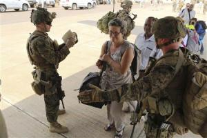 Marines and sailors with Special-Purpose Marine Air-Ground Task Force Crisis Response help U.S. citizens into a Marine Corps KC-130J Hercules airplane in Juba