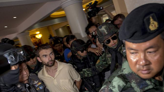 An arrested suspect of the recent Bangkok blast is detained by military personnel at the Metropolitan Police Bureau in central Bangkok
