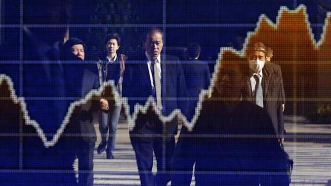 Pedestrians are reflected in an electronic board showing a graph of recent fluctuations of Japan's Nikkei average outside a brokerage in Tokyo December 12, 2013.