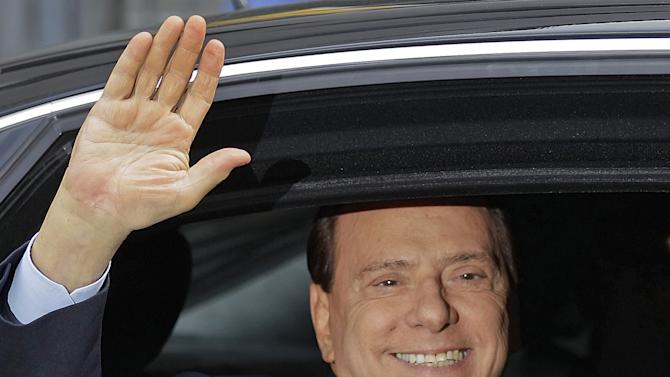 FILE - In this  Sept. 19, 2011 file photo, Italian Premier Silvio Berlusconi waves from his car as he leaves the Milan's tribunal, Italy, after attending an hearing of the trial where he is accused of bribing British lawyer Robert Mills. When Silvio Berlusconi resigned after dominating the political scene for two decades, he left a country in financial shambles and a personal legacy tarnished by a sex and corruption scandals. Commentators called it the end of an era. Eight months later the political world is abuzz with signs that the 75-year-old media mogul is considering a comeback, plotting a return to power that even his closest allies had considered impossible. (AP Photo/Luca Bruno, File)